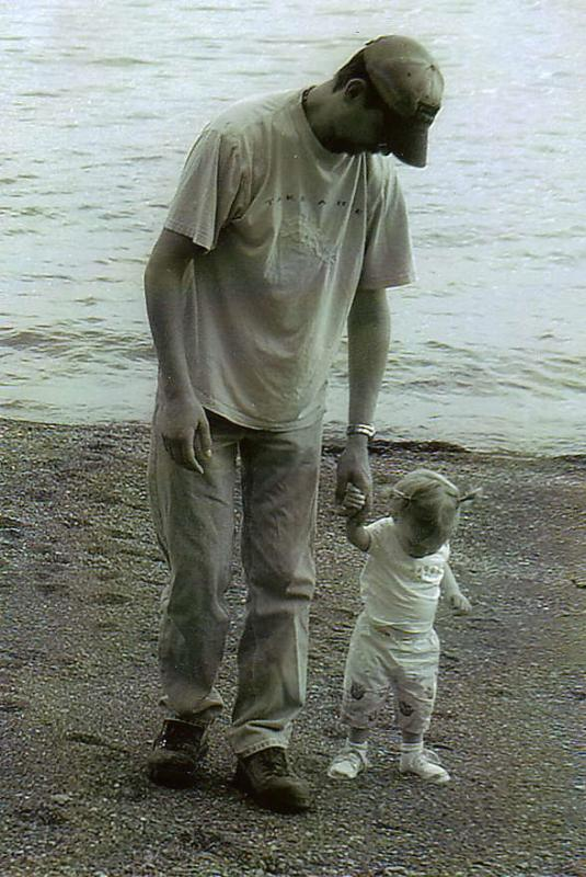 father at beach walking hand in hand with toddler