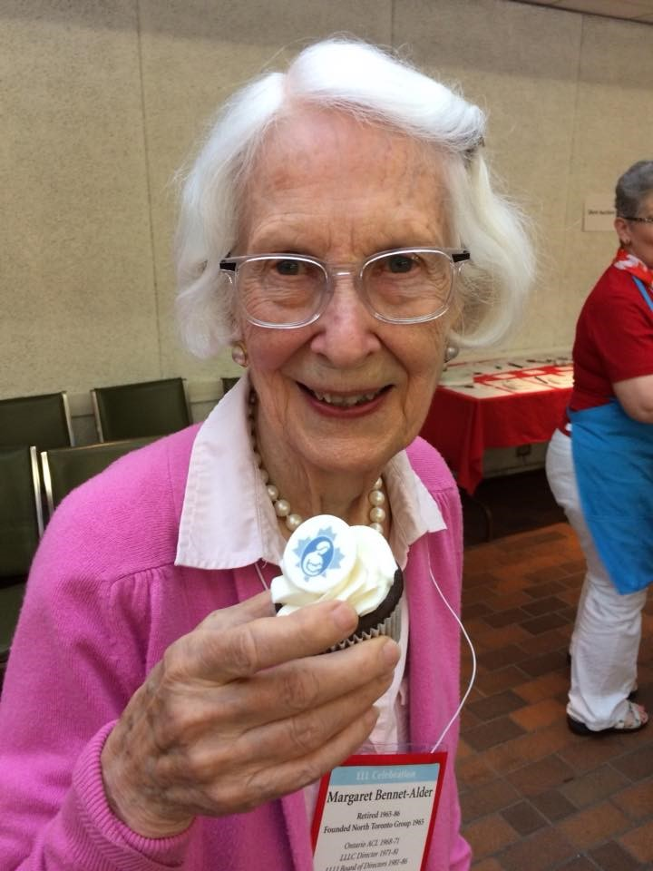 Margaret Bennet-Alder celebrating her 90th birthday with fellow La Leche League Leaders holding a cupcake