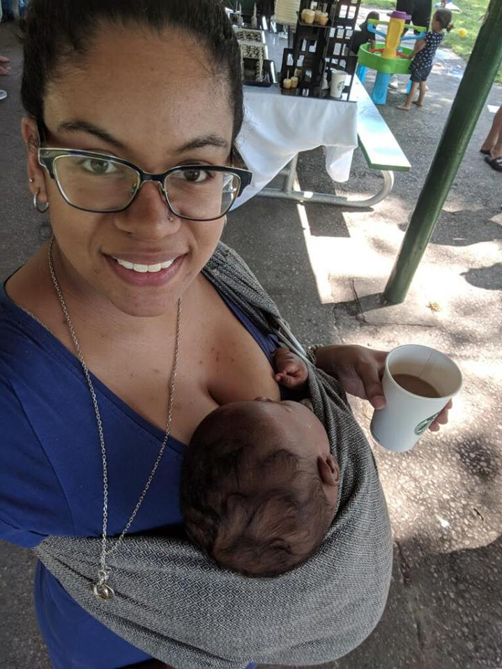 Taleah a black breastfeeding La Leche League Leader carries her two month old son in a sling while enjoying a coffee.